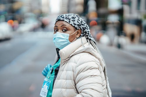 Side view thoughtful African American nurse wearing protective respirator and gloves crossing road in modern city and looking at camera