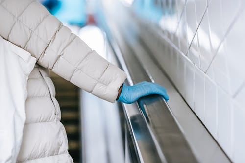 Back view of crop anonymous ethnic female medic in padded coat and latex glove touching handrail of moving stairs in underground