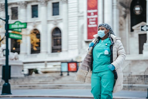Plus size black female medic in uniform strolling on urban roadway while looking away during COVID 19 pandemic