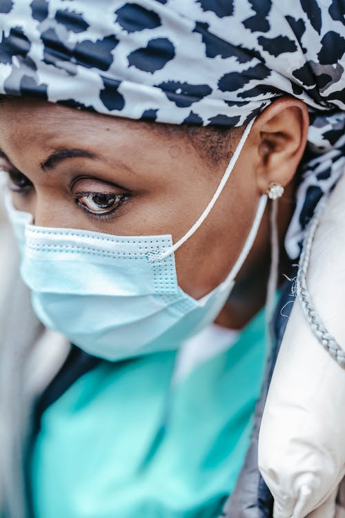Crop focused mature ethnic female doctor in sterile mask and kerchief looking away during coronavirus pandemic