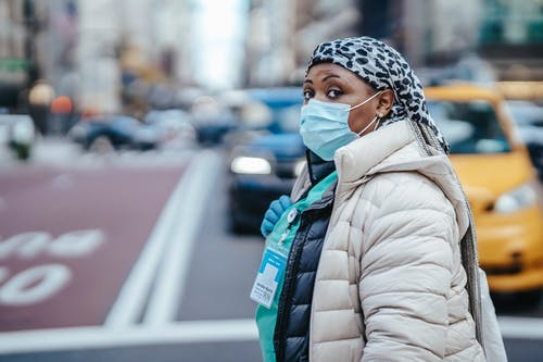 Side view of mature black female medic in outerwear with badge looking at camera on urban roadway