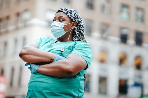 Self confident African American female doctor in uniform with folded arms looking away in town