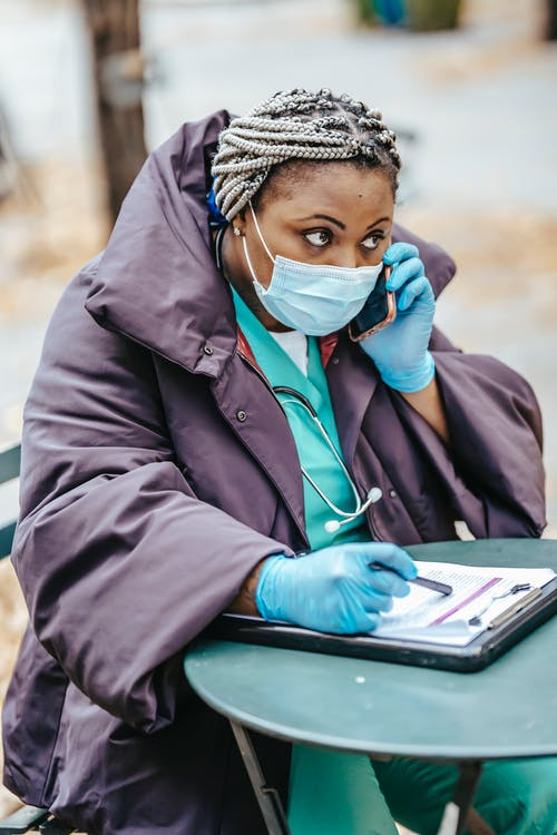 Attentive black doctor speaking on smartphone in city