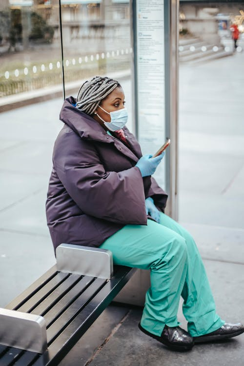 Black doctor with smartphone on street bench