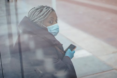 Through glass wall side view of mature ethnic female medic in outerwear with cellphone looking away in town