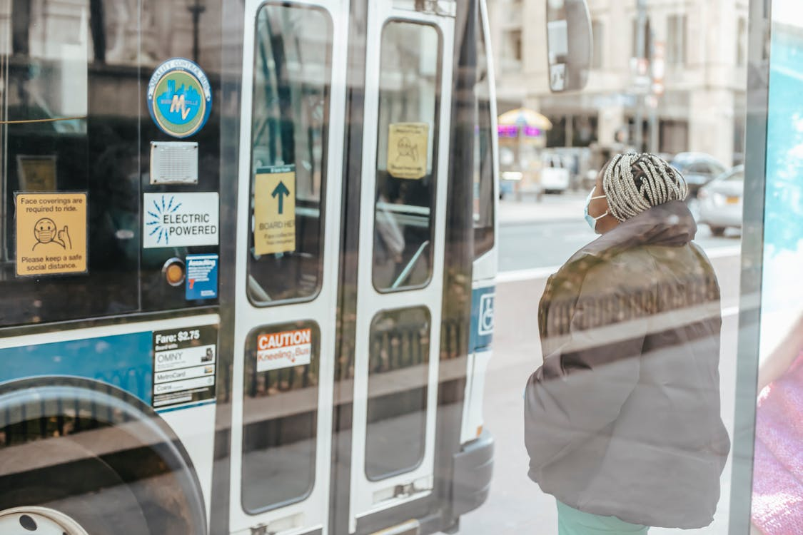 Through glass wall back view of anonymous ethnic female medic standing against public transport in town