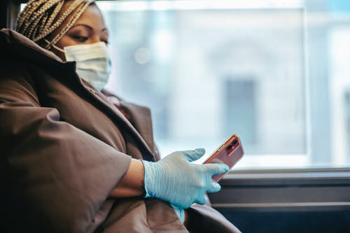 Crop black doctor chatting on smartphone in public transport