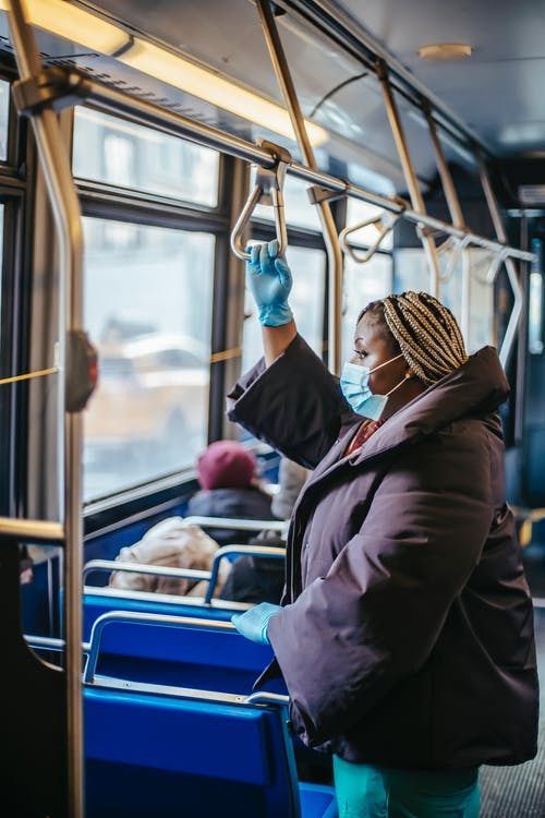 Side view of overweight ethnic female doctor in sterile mask and gloves looking forward in public transport