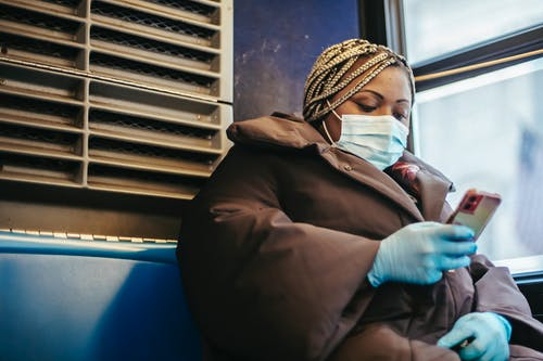 African American woman with phone riding bus in pandemic