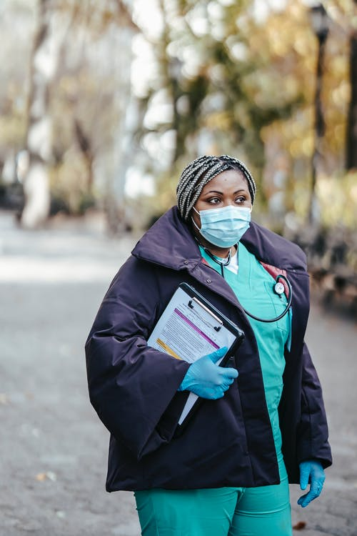 Adult black lady doctor in medical outfit and protective mask with stethoscope and gloves strolling in street on walkway with documents in clipboard in daylight