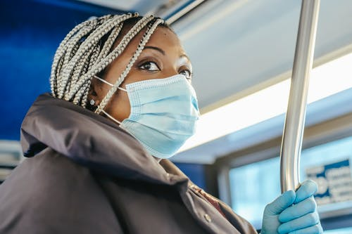 Adult black woman in warm outfit and protective mask with gloves riding on public bus in daytime