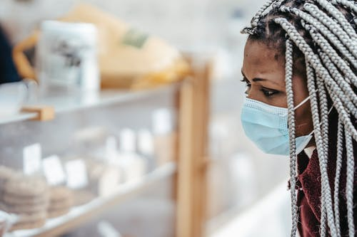 Side view of adult black female in warm coat wearing protective mask while examining baking goods in street market in daytime