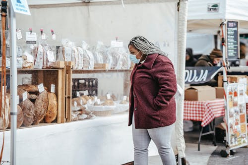Side view of adult African American woman wearing protective mask and warm coat walking in street market while selecting bakery products in daylight