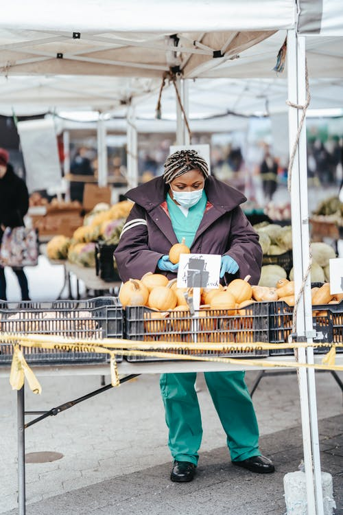 African American female nurse choosing products in street market