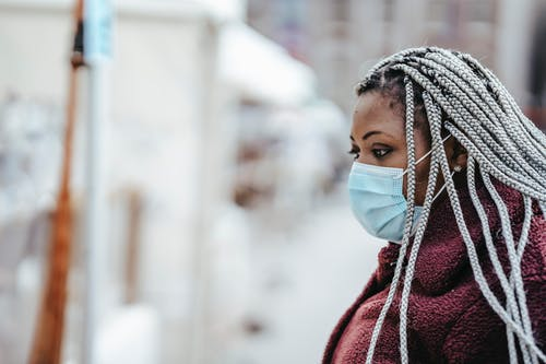 Black female in mask outdoors in epidemic