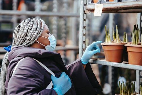 Unrecognizable black lady choosing plants in market