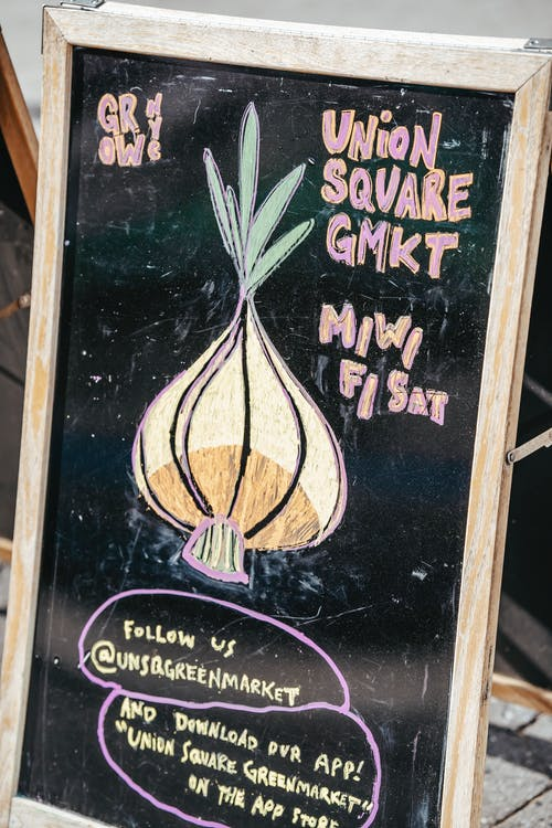 Chalkboard with colorful onion and local market invitation placed in street in daytime