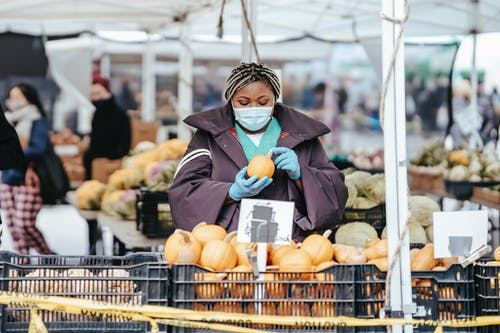 Adult African American female nurse in medical uniform and gloves with mask choosing pumpkin from box while standing in daylight in street market