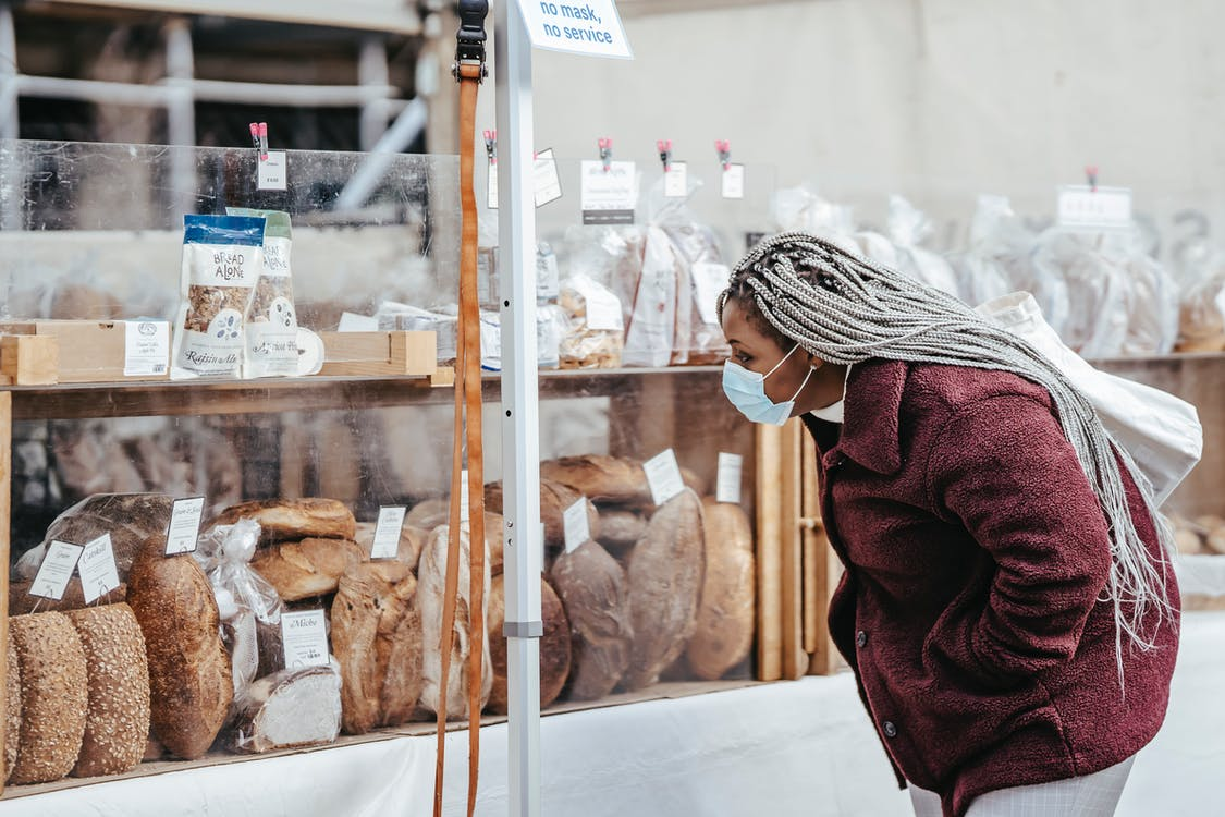 Side view of adult black lady wearing protective mask and warm coat selecting baking goods while standing in street market in daytime