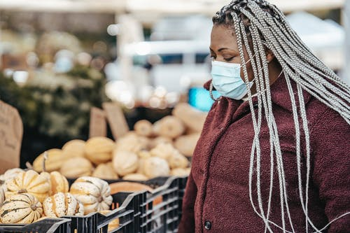 Black woman in medical mask choosing pumpkins in street market