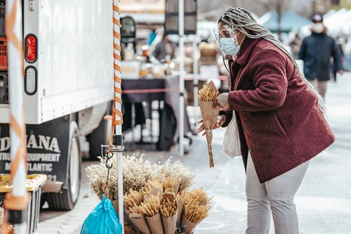Black adult lady in warm coat and protective mask standing in street market and choosing bouquet of dried corn in daytime