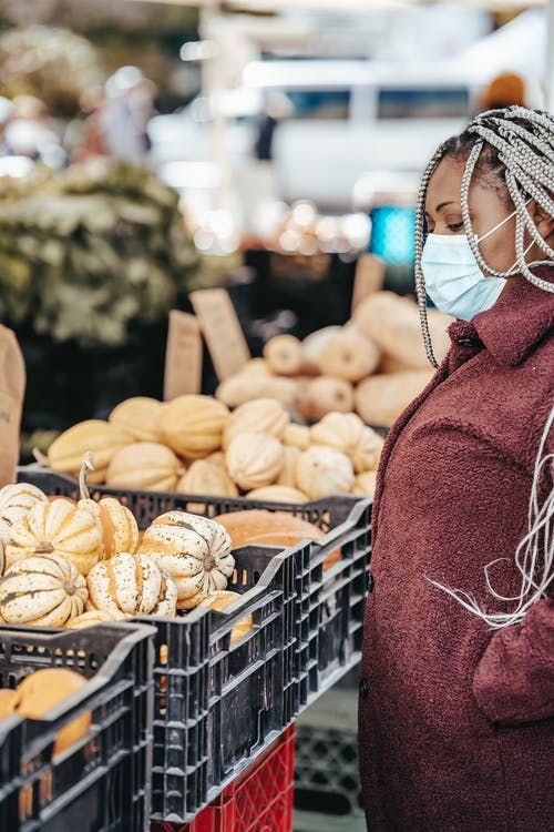 African American female in mask picking vegetables on market