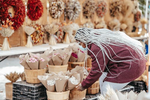 Side view of adult faceless black lady in warm coat and protective mask picking dry bouquet while standing in street market in daylight