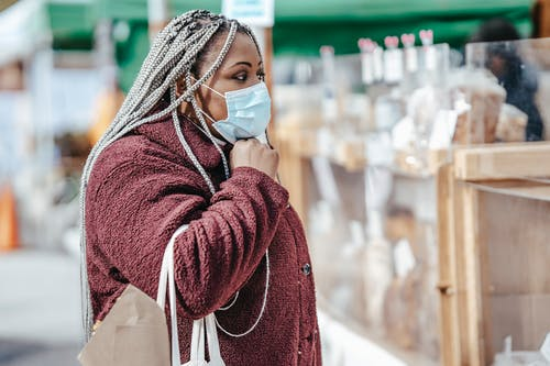 Black woman standing near pastry on market in mask