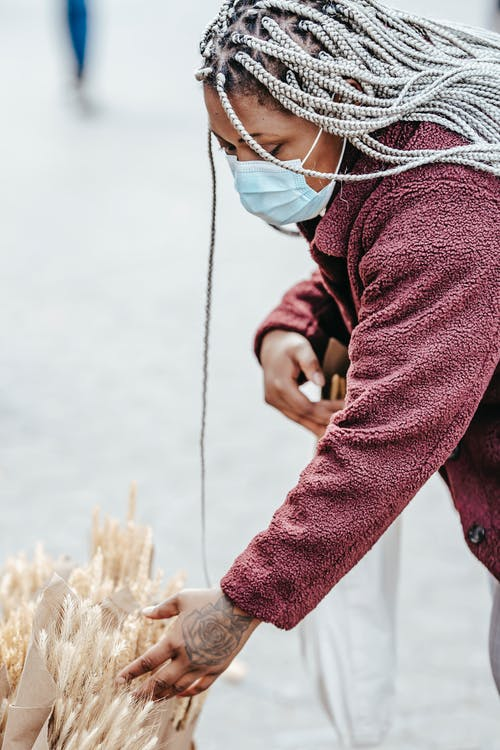Black lady picking bouquet of dried wheat in street