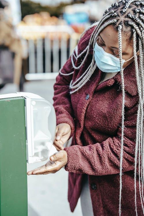 Black female in mask using sanitizer in street