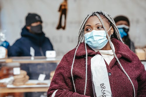 Black woman in pandemic standing with bread in market