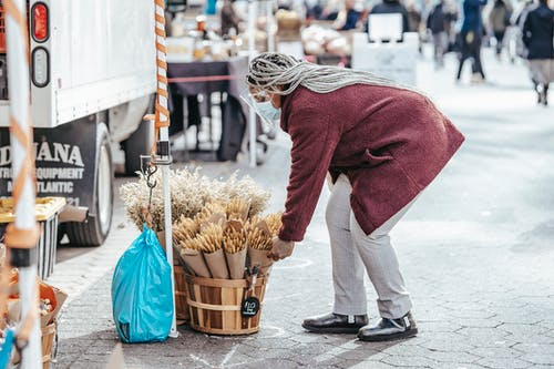 Black female selecting bouquet of dried wheat in street