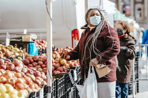 Side view of African American lady with braids in warm jacket with bags in hand looking away while choosing fruits near stall on street market