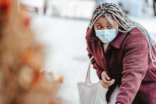 Black woman choosing goods on street market