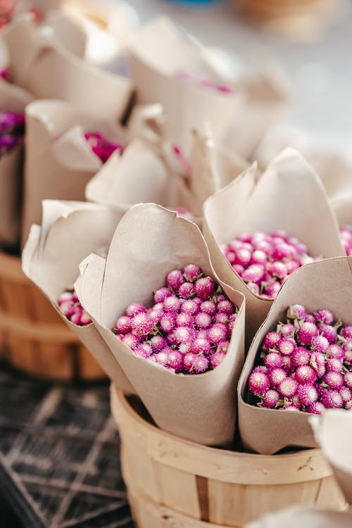 From above bouquets of little fresh pink flowers wrapped in paper placed in wooden baskets on street market at daytime