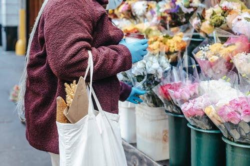 Woman with paper cup of coffee buying flowers on street
