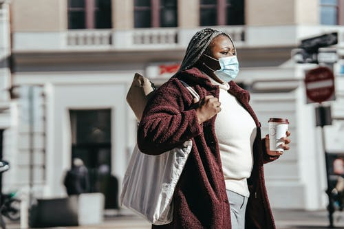 Side view of African American female in casual clothes and medical mask walking on street with shopping bag and paper cup of drink