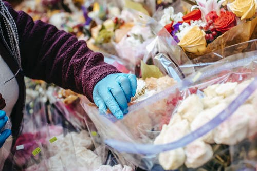 Anonymous female in casual clothes and medical gloves picking up flowers in floral shop in open market on street