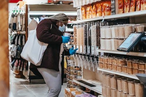 Black woman choosing grains in supermarket