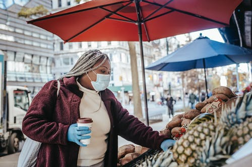 Side view of African American female in casual outfit and dreadlocks wearing medical mask and latex gloves choosing food in street stand with fruit and vegetables