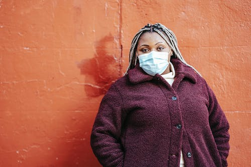 Pensive African American female with dreadlocks in casual clothes and protective mask standing near red painted wall on street and looking at camera