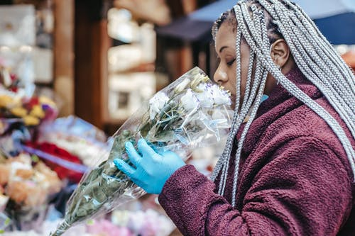 Side view of African American female with dreadlocks and in casual wear and blue latex gloves smelling bouquet of fresh flowers in street floral shop