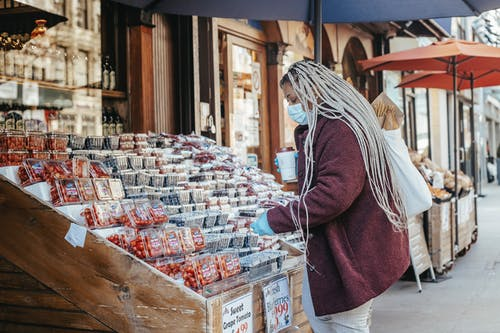 Black woman buying fruits in street stall