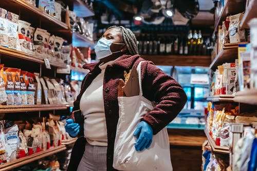 African American female buyer with shopping bag and smartphone in protective mask and gloves selecting products in supermarket