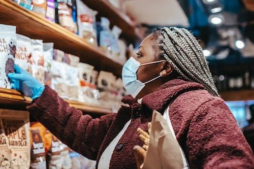 Black woman choosing chia seeds in shopping mall