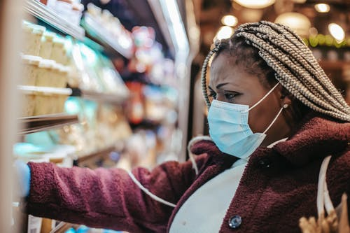 Black frown woman choosing purchases in supermarket