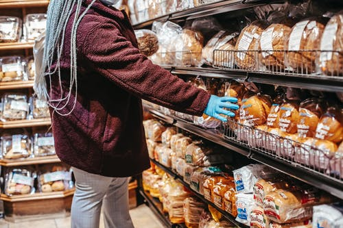 Side view of crop anonymous female customer picking loaf of bread in supermarket during coronavirus epidemic