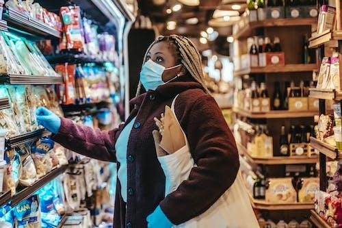 Black woman choosing products in supermarket