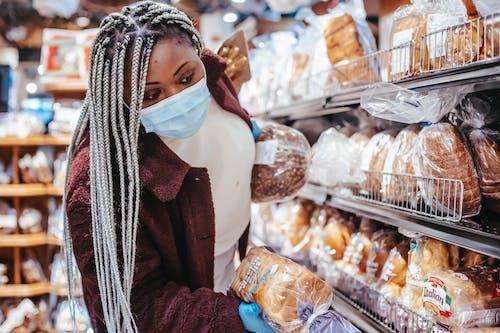 Black woman choosing bread in baking department