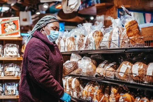 Black woman buying bread in supermarket